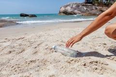 递拾起在海滩的妇女塑料瓶清洁,志愿概念 生态和地球日概念 库存照片