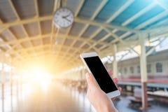 递拿着一个巧妙的电话在一个火车站的一个时钟下与温暖和冷光 背景概念查出的目的程序时间白色 库存照片