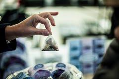递拿着一个花卉茶包在市场上 图库摄影