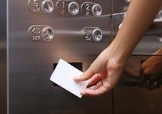 递拿着一张钥匙卡片上上下下打开电梯地板befor 图库摄影