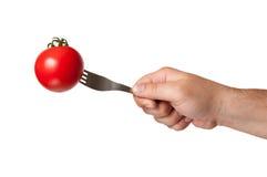 递拿着一把叉子用在它stucked的蕃茄 库存图片