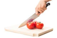 递拿着一把大刀子、三个蕃茄和木板 库存照片
