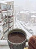 递拿着一杯咖啡反对城市视图在胜利的雪下 免版税图库摄影