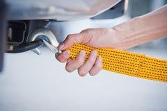 递拿着与汽车的黄色汽车拖曳皮带 库存图片
