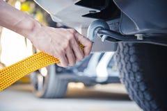 递拿着与汽车的黄色汽车拖曳皮带 免版税图库摄影