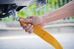 递拿着与汽车的黄色汽车拖曳皮带 免版税库存图片