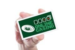 递拿着与轮盘赌和四一点的网上赌博娱乐场卡片 库存照片