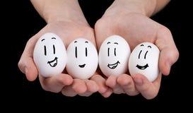 递拿着与滑稽的面孔面带笑容的逗人喜爱的鸡蛋 库存图片