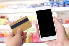 递拿着信用卡和巧妙的电话有黑屏的 图库摄影