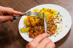 递拿着叉子和刀子有烤鸡胸脯的用土豆在一块板材在木背景 图库摄影