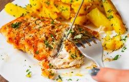 递拿着叉子和刀子有烤鸡胸脯的用土豆在一块板材在木背景 库存图片