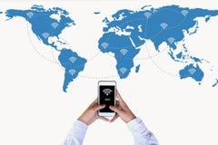 递拿着在世界地图网络和无线通讯网络的巧妙的电话 免版税图库摄影