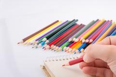 递拿着在五颜六色的铅笔旁边的一支铅笔 图库摄影