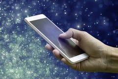 递拿着在抽象bokeh和星轻的backgro的智能手机 免版税库存图片