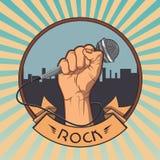 递拿着在拳头减速火箭的岩石的一个话筒 免版税库存图片