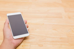 递拿着在木桌背景的巧妙的手机与Co 免版税图库摄影