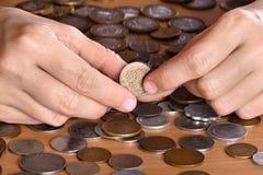 递拿着在硬币中堆的一枚硬币  库存图片
