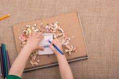 递拿着在螺纹笔记本的一支颜色铅笔 库存照片