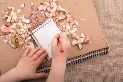 递拿着在螺纹笔记本的一支颜色铅笔 库存图片
