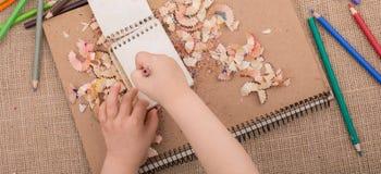 递拿着在螺纹笔记本的一支颜色铅笔 免版税库存图片