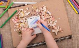 递拿着在螺纹笔记本的一支颜色铅笔 免版税图库摄影