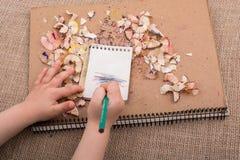 递拿着在螺纹笔记本的一支颜色铅笔 免版税库存照片