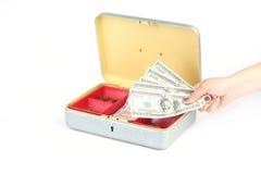 递拿着在钱箱前面的美元在白色 免版税库存图片