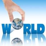 递拿着在题字世界的背景的行星地球。 库存图片