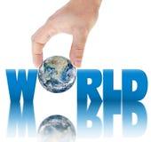递拿着在题字世界的背景的行星地球。 图库摄影
