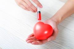 递拿着塑料注射器红色心脏的医疗射入 库存照片