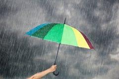 递拿着多彩多姿的伞在与雨的黑暗的天空下 免版税库存照片