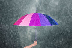 递拿着多彩多姿的伞在与雨的黑暗的天空下 免版税库存图片