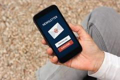 递拿着巧妙的电话与订阅在sc的时事通讯概念 免版税库存图片