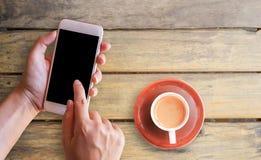 递拿着巧妙的电话和咖啡 免版税库存照片