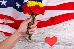 递拿着康乃馨花束在一个美国人的背景的有被雕刻的心脏的 图库摄影