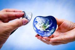 递拿着心脏地球和听心脏的人 图库摄影