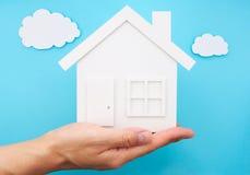 递拿着房子反对天空由纸制成 免版税库存图片