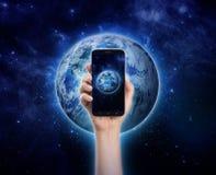 递拿着手机或巧妙的电话在行星地球backgro 库存图片
