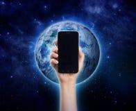 递拿着手机或巧妙的电话在行星地球backgro 免版税图库摄影