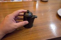 递拿着日本酱油有盒盖的陶瓷茶壶 免版税库存图片