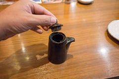 递拿着日本酱油有盒盖的陶瓷茶壶 库存图片