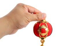 递拿着春节在白色隔绝的装饰的一个红色球状形状灯笼 图库摄影