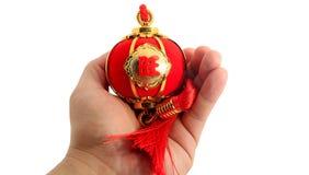 递拿着春节在白色隔绝的装饰的一个红色球状形状灯笼 免版税图库摄影