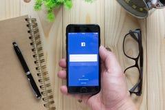 递拿着显示在人手藏品的苹果计算机iPhone7 Facebook屏幕 免版税库存图片