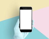 递拿着智能手机在淡色背景蓝色,桃红色,黄色的黑屏 技术概念为现代是美好 免版税库存照片