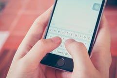 递拿着智能手机,当发短信时 图库摄影