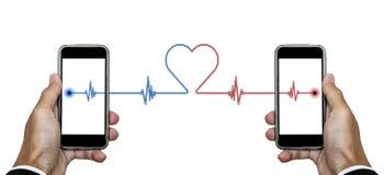 递拿着有信号线的与另一个电话的连接巧妙的电话与心脏形状,在白色背景 免版税库存图片