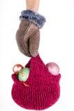递拿着有圣诞节装饰的一个被编织的帽子 免版税库存图片
