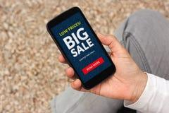 递拿着有大销售概念的巧妙的电话在屏幕上 库存照片