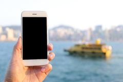 递拿着有小船和地平线背景的大模型智能手机 库存图片